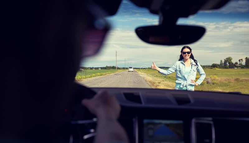 Woman hitchhiking and stopping car with thumbs up stock images