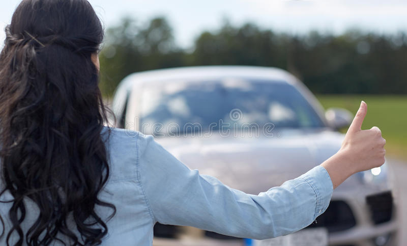 Woman hitchhiking and stopping car with thumbs up royalty free stock images
