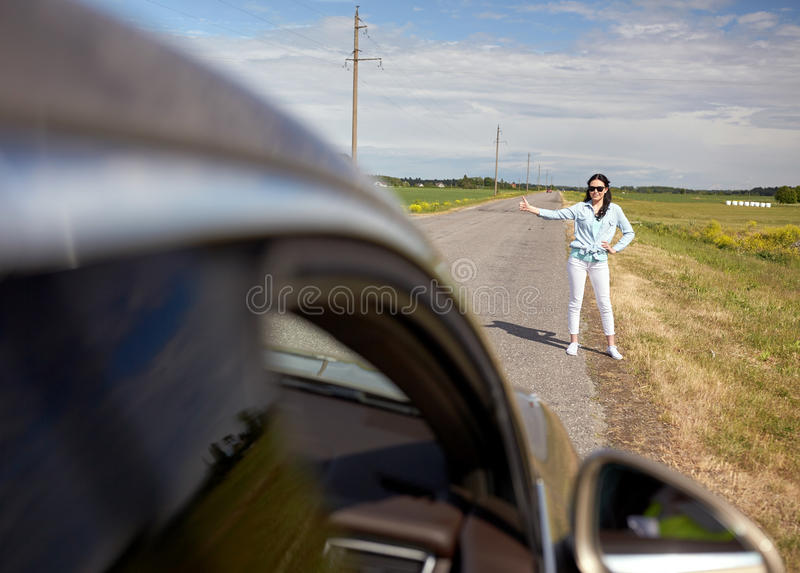 Woman hitchhiking and stopping car with thumbs up. Road trip, travel, gesture and people concept - woman hitchhiking and stopping car with thumbs up gesture at royalty free stock photo