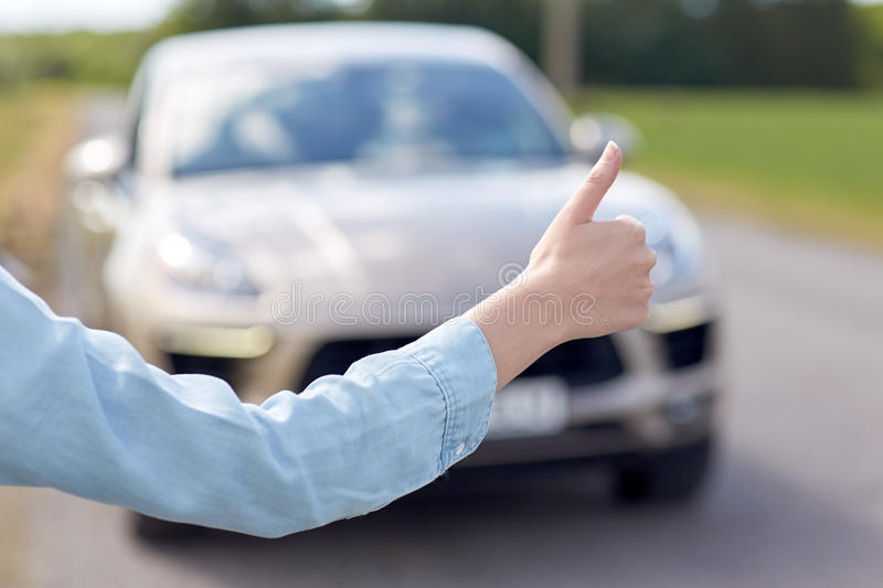 Woman hitchhiking and stopping car with thumbs up. Road trip, travel, gesture and people concept - woman hitchhiking and stopping car with thumbs up gesture at royalty free stock image