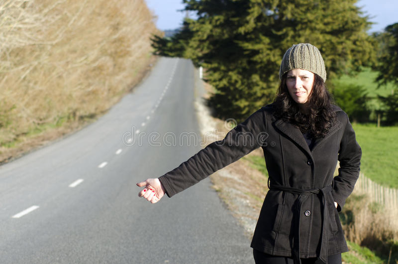 Woman hitchhiking. Young woman hitchhiking in rural countryside area in New Zealand during autumn season royalty free stock photos