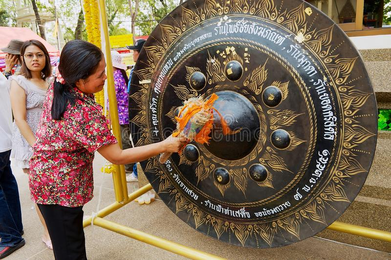 Woman hits gong with a hammer visiting Wat Pho Chai buddhist temple in Nong Khai, Thailand. royalty free stock photo