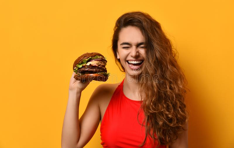 Woman hold big barbecue burger sandwich with hungry mouth happy screaming laughing on yellow background. Fast food concept stock images