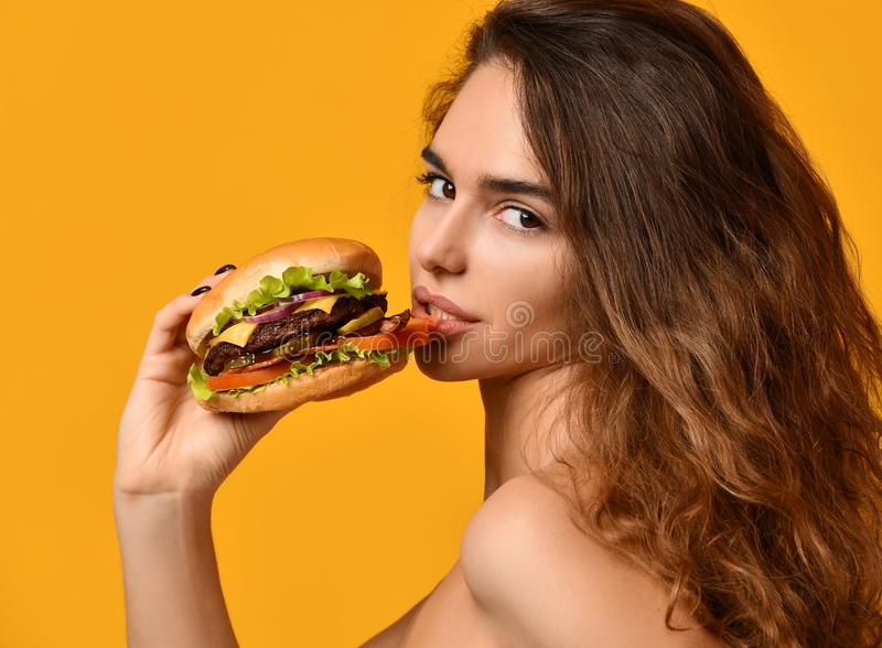 Woman hold big barbecue burger sandwich with hungry mouth happy screaming laughing on yellow background royalty free stock image