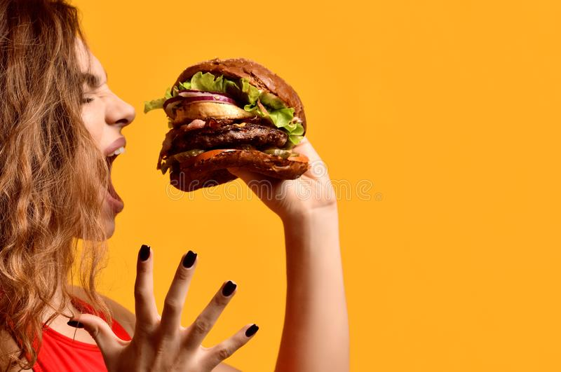 Woman hold big beef burger sandwich with hungry mouth happy screaming laughing on yellow background stock photo