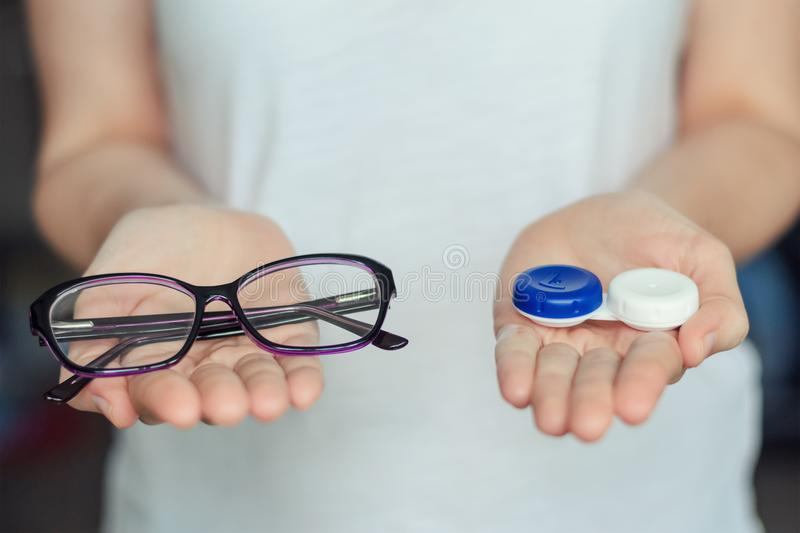 Woman hold contact lenses and glasses in hands. concept of choice of vision protection stock images