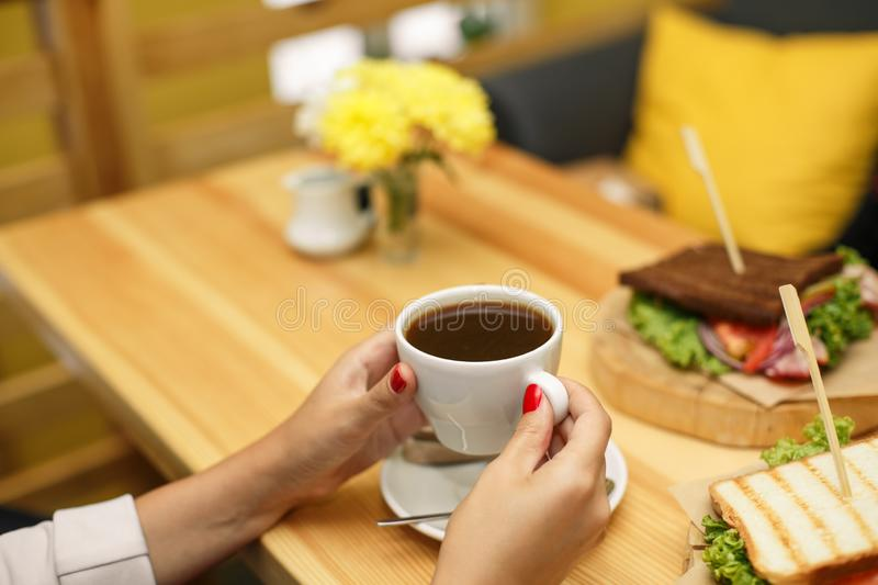 Woman hold a cup of coffee at backgroud wooden table, on which lies a sandwich stock images