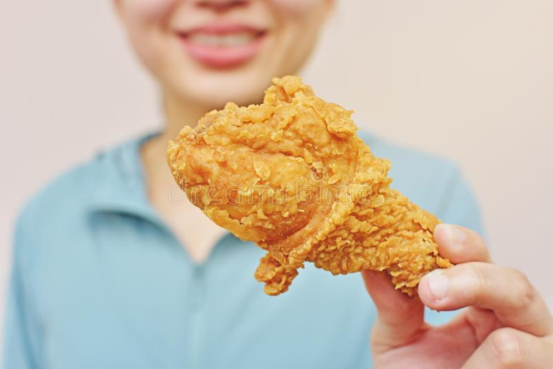 A woman hold fried chicken leg or drumstick stock photography