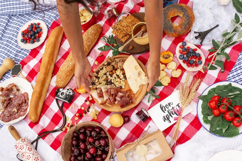 Woman hold plate with parma and cheese. Summer outdoor picnic royalty free stock image