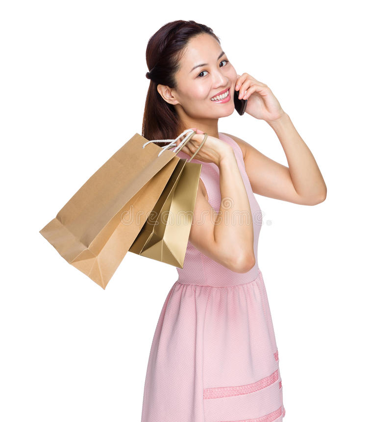Woman hold with shopping bag and talk to cellphone stock photography
