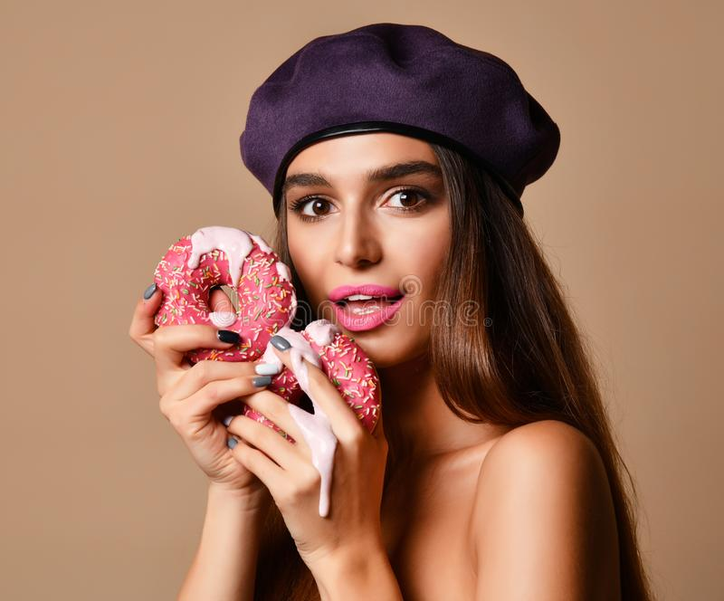Woman hold Sweet pink sugar donuts hungry mouth on light brown background. Closeup composition of Fast food concept stock photography