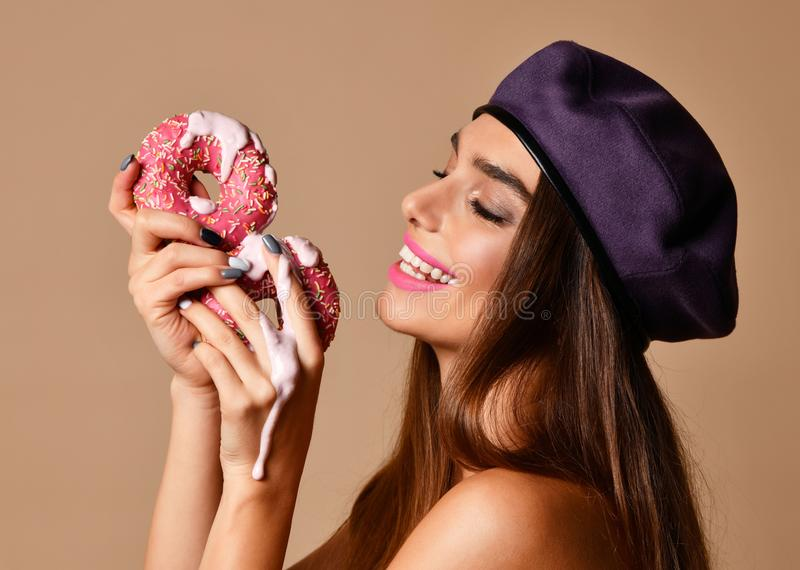Woman hold Sweet pink sugar donuts hungry mouth on light brown background. Closeup composition of Fast food concept stock image