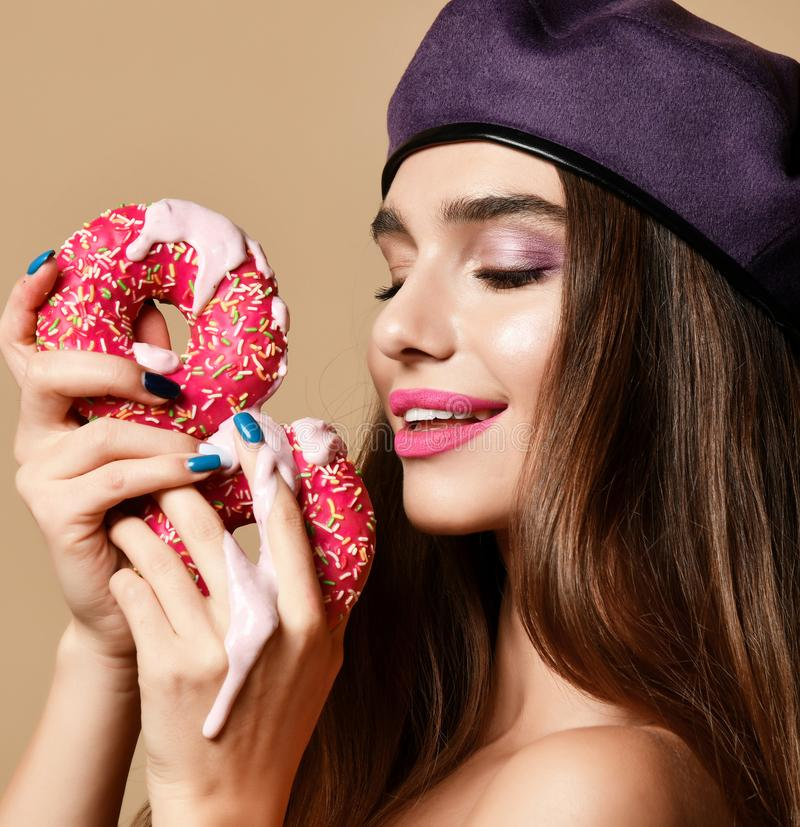 Woman hold Sweet pink sugar donuts hungry mouth on light brown background. Closeup composition of Fast food concept stock images