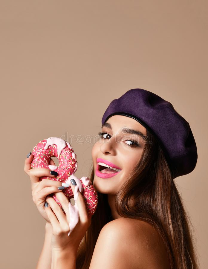 Woman hold Sweet pink sugar donuts hungry mouth on light brown background. Closeup composition of Fast food concept stock photos