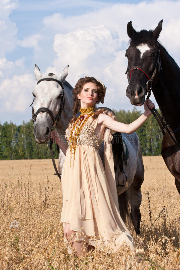 The woman hold two horses. The woman in a beautiful old style dress with two horses in yellow field stock image