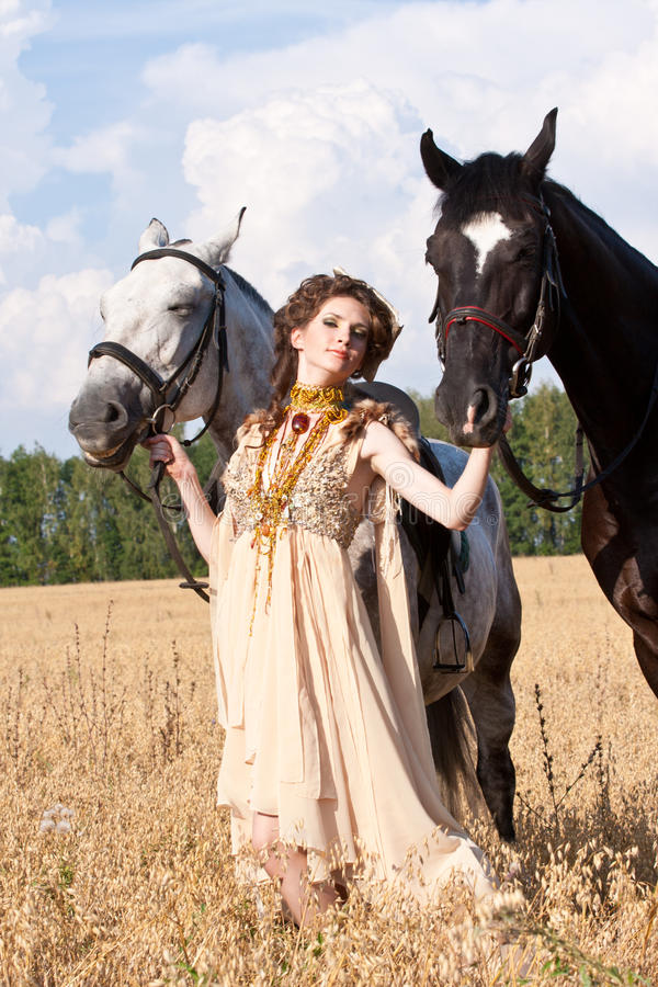 The woman hold two horses. The woman in a beautiful old style dress with two horses in yellow field royalty free stock photos