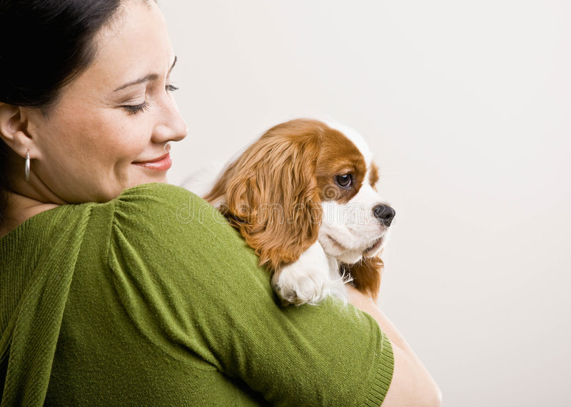Woman hold up puppy. Devoted woman holding and comforting pet dog royalty free stock images