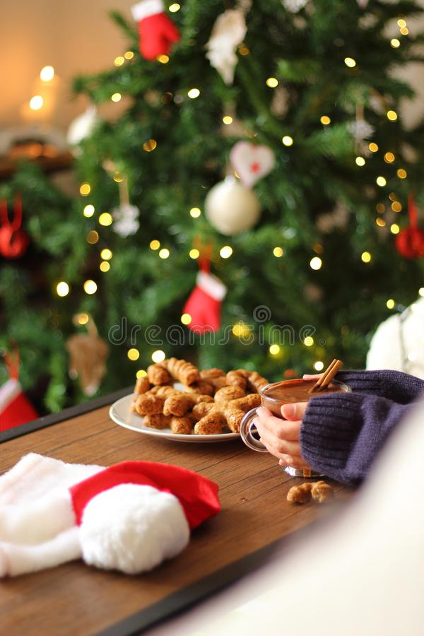 Woman holdin cup of hot chocolate on wooden table with gingerbreads indoors. stock image