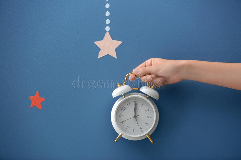 Woman holding alarm clock on color background stock photo
