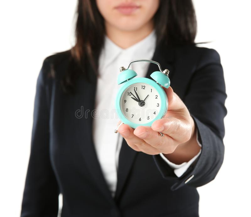 Woman holding alarm clock on white background. Time management concept stock photos