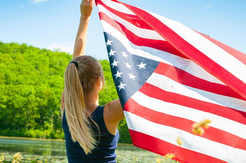 Woman holding American flag outdoors. United States celebrate 4th of July Independence Day. Young woman holding American flag outdoors. United States celebrate stock image