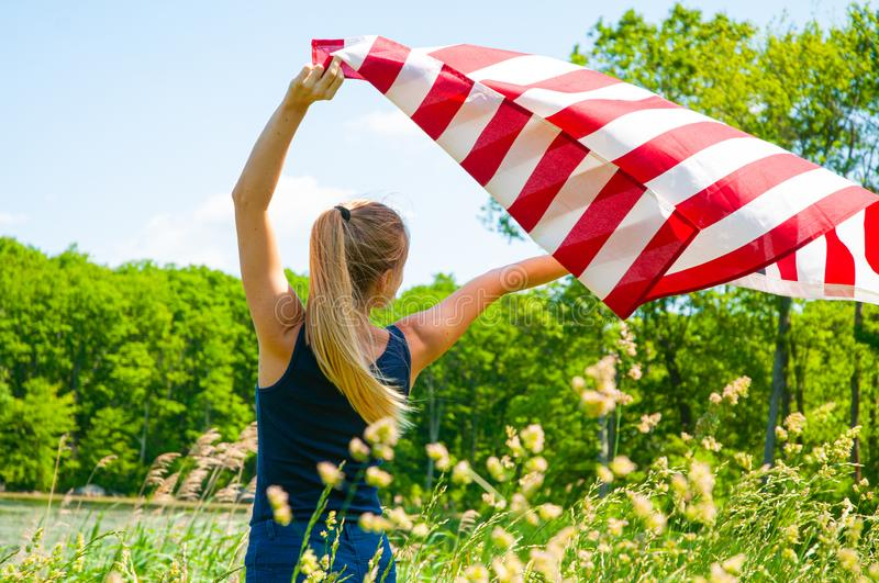 Woman holding American flag outdoors. United States celebrate 4th of July Independence Day. Young woman holding American flag outdoors. United States celebrate stock photos