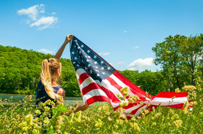 Woman holding American flag outdoors. United States celebrate 4th of July Independence Day. Young woman holding American flag outdoors. United States celebrate royalty free stock images