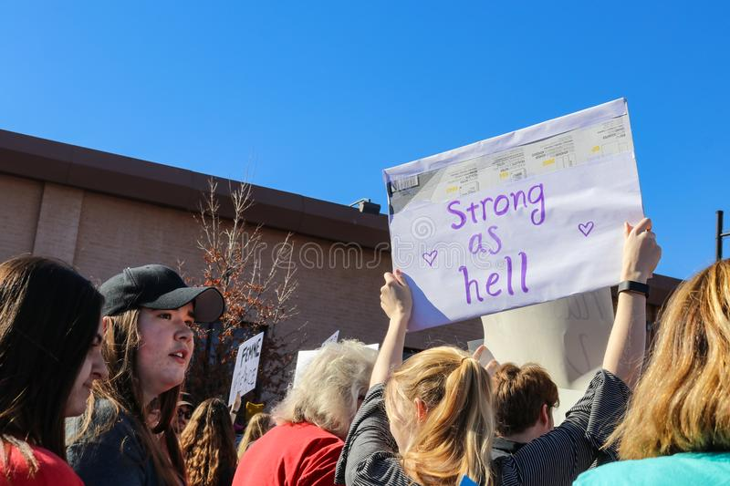 Woman holding sign that says Strong as Hell in Womens March in Tulsa Oklahoma USA 1-20-2018. A Woman holding sign that says Strong as Hell in Womens March in stock photo