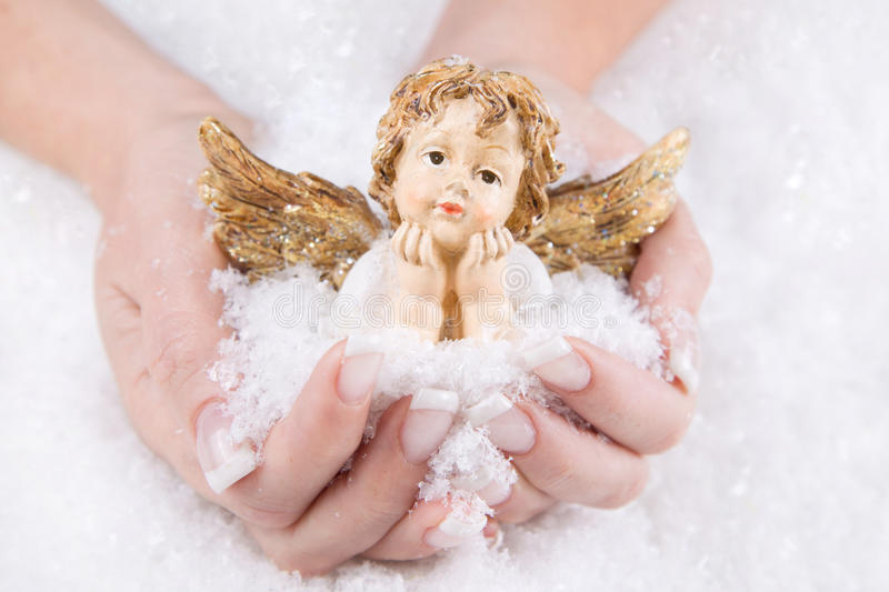 Woman holding an angel for christmas in her hands royalty free stock images