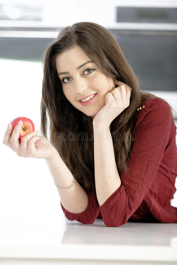 Woman holding an apple. Beautiful young woman eating an apple in her white kitchen royalty free stock image