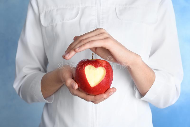 Woman holding apple with carved heart on color background stock image