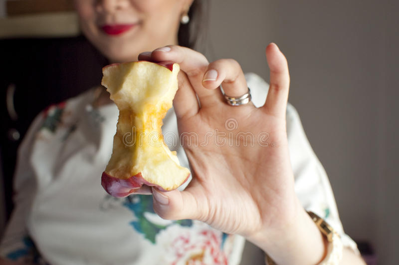 Woman holding an apple core. Woman smiling and holding an apple core royalty free stock photos