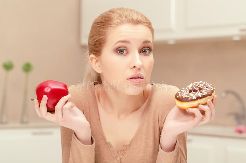 Woman holding apple and a donut royalty free stock photography
