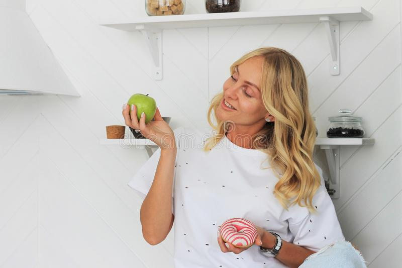 Woman holding apple and donut in her hands in healthy fruit versus sweet junk food temptation in fitness, body health care and royalty free stock photos