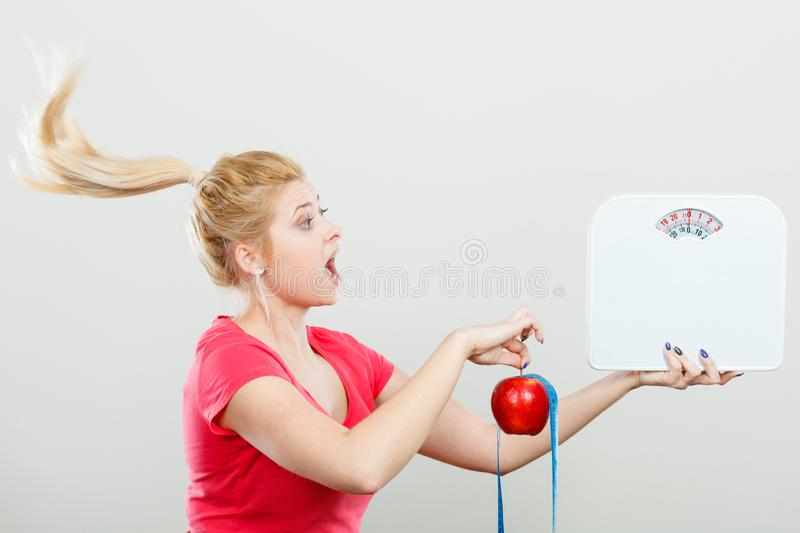 Woman holding apple,measuring tape and weight machine royalty free stock photography