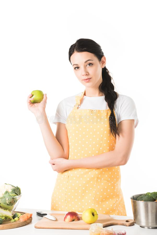 Woman holding apple near table with cutting board saucepan apples. And vegetables stock image