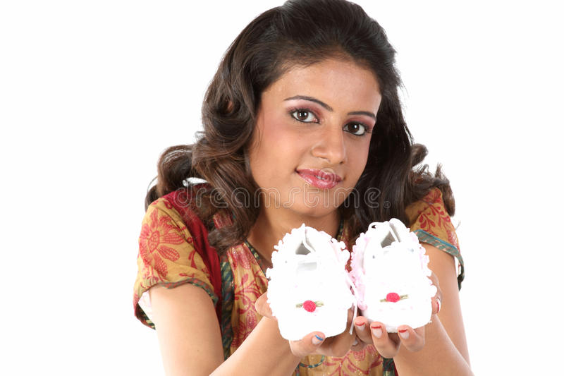 Woman holding baby shoes royalty free stock image