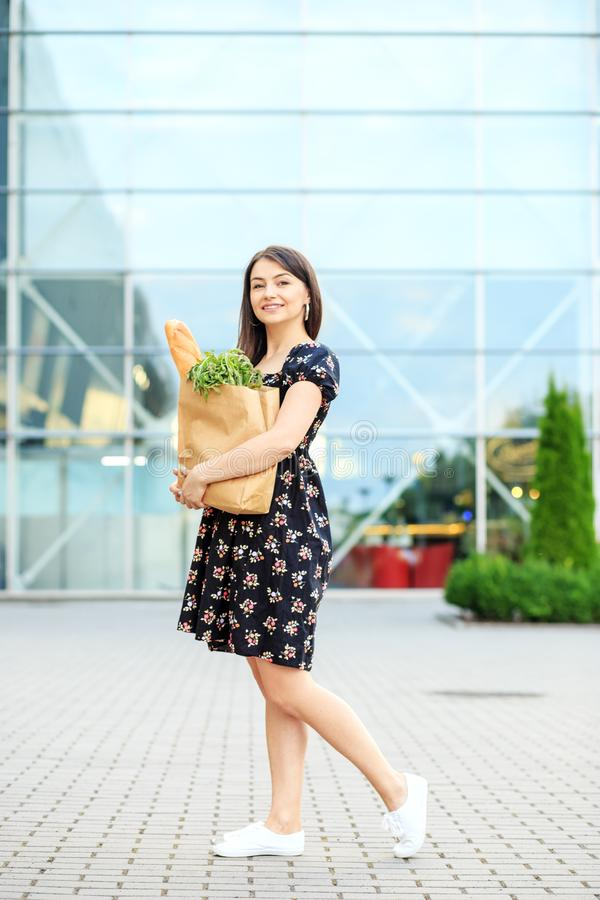 Woman holding bag with baguette and food. A girl in a dress. The concept of shopping, lifestyle. Woman holding bag with baguette and food. A girl in a dress. The stock photography