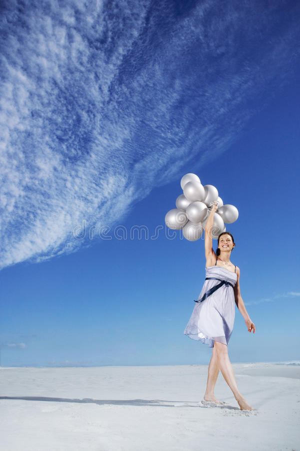 Woman Holding Balloons On Beach Stock Photo