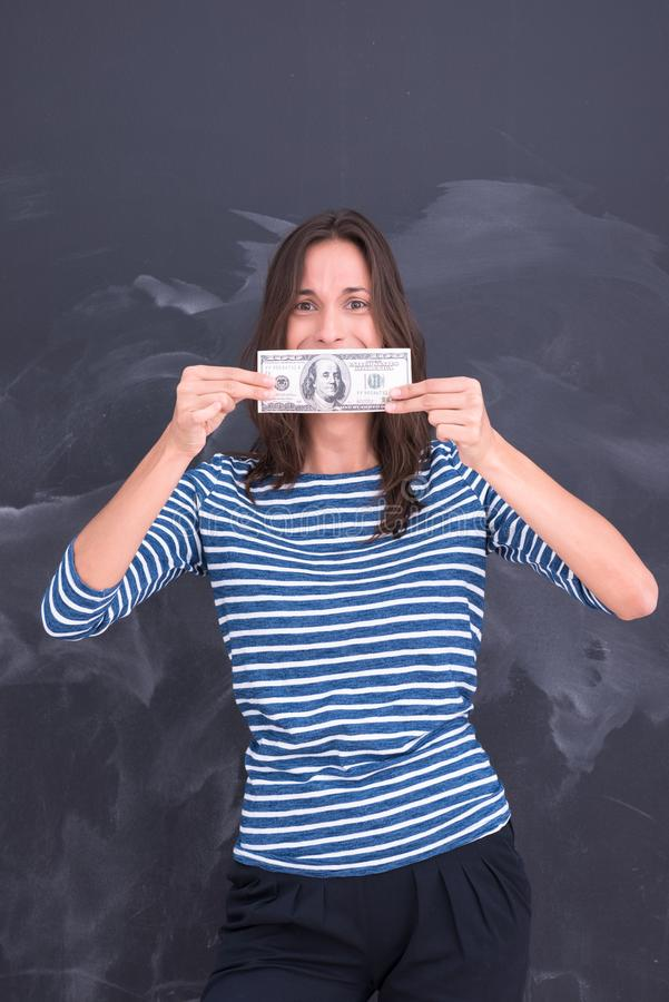 Woman holding a banknote in front of chalk drawing board. Portrait of a young woman holding a banknote in front of chalk drawing board stock photos