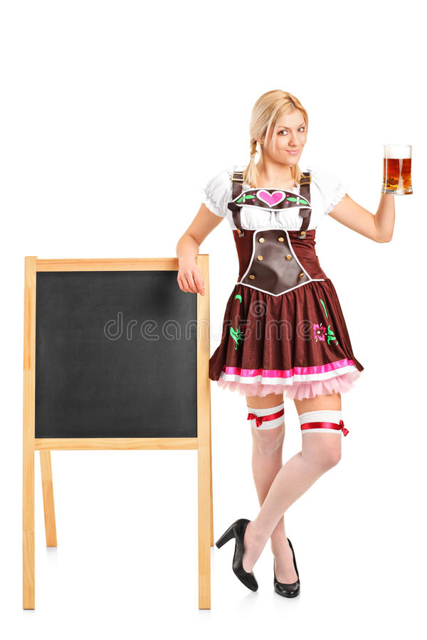 Woman holding a beer glass. Full length portrait of a woman wearing traditional costume and holding a beer glass on white background royalty free stock images