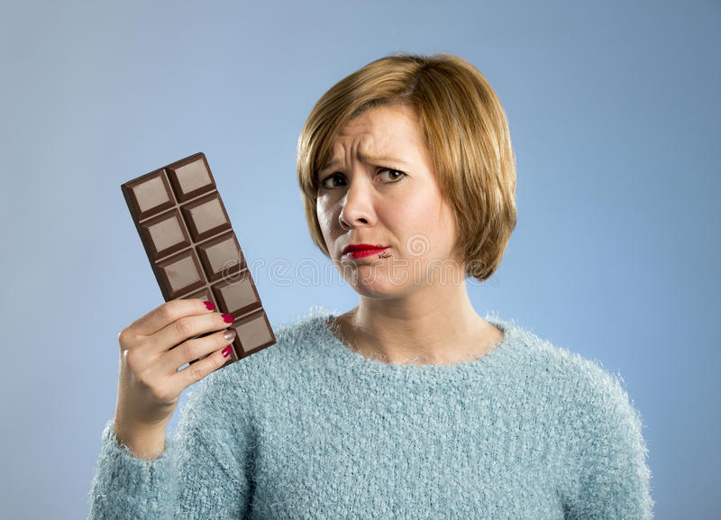 Woman holding big chocolate bar with mouth stains and guilty face expression in sugar addiction. Young cute woman holding big chocolate bar with mouth stains and royalty free stock photos