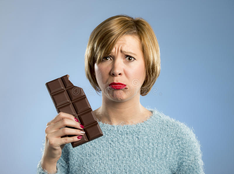 Woman holding big chocolate bar with mouth stains and guilty face expression in sugar addiction. Young cute woman holding big chocolate bar with mouth stains and royalty free stock image