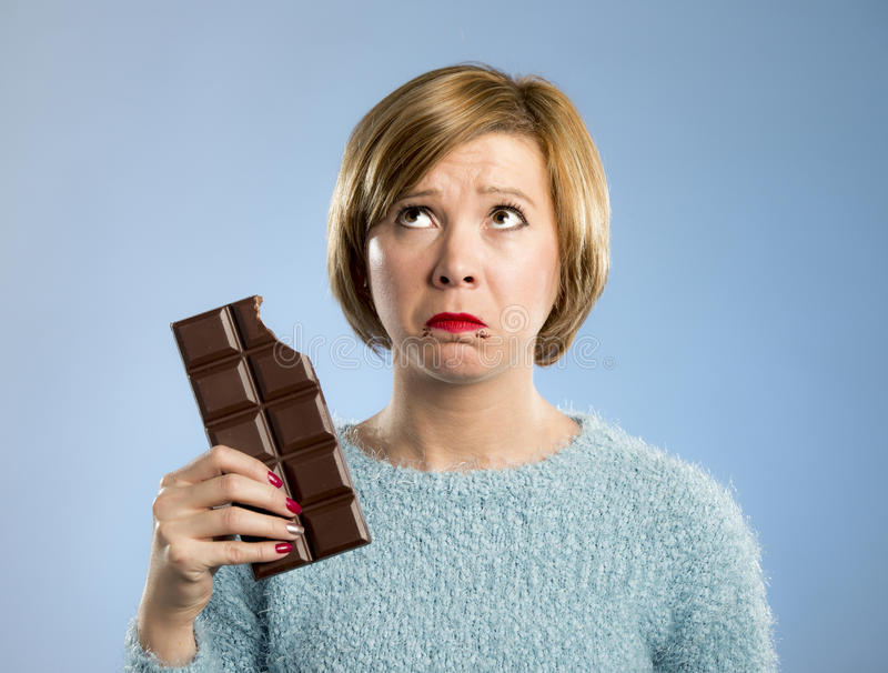 Woman holding big chocolate bar with mouth stains and guilty face expression in sugar addiction. Young cute woman holding big chocolate bar with mouth stains and royalty free stock images
