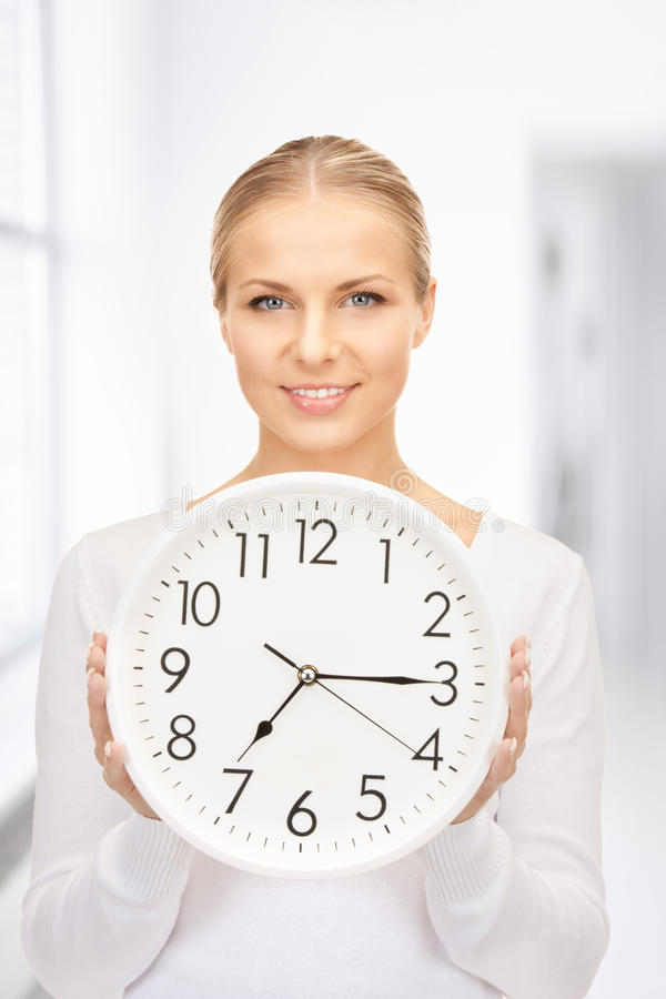 Woman holding big clock. Picture of woman holding big clock in office stock image