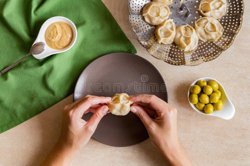 Woman eat tasty Manti steam cooked meat dumplings royalty free stock image