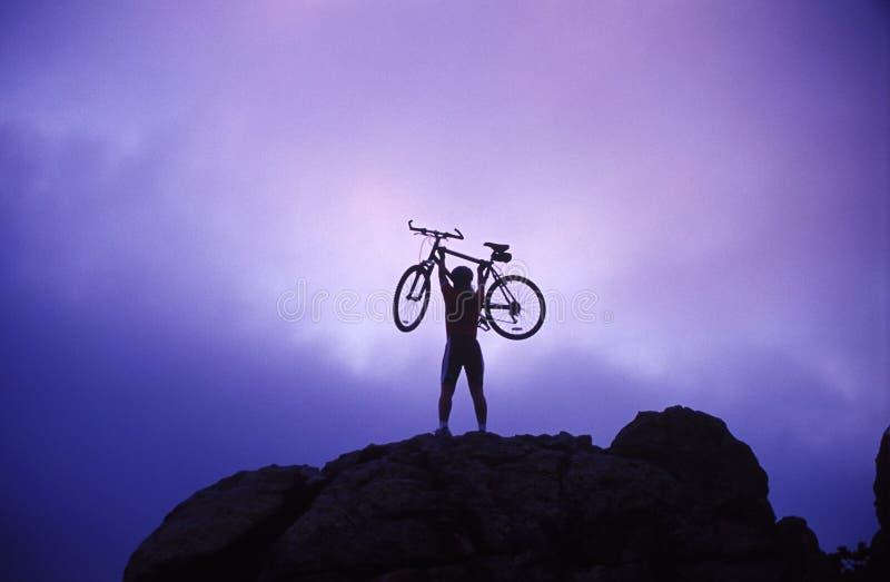 Woman holding bike overhead stock image