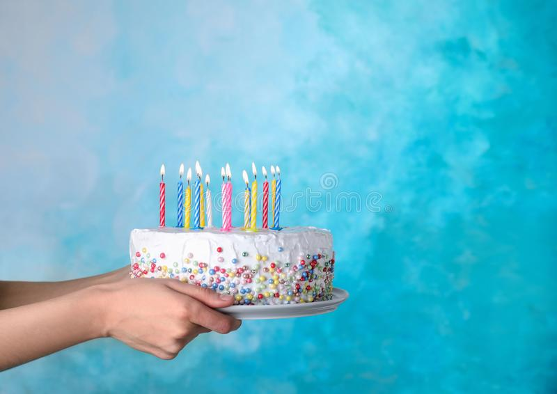 Woman holding birthday cake with burning candles on light blue background, closeup. Space royalty free stock image