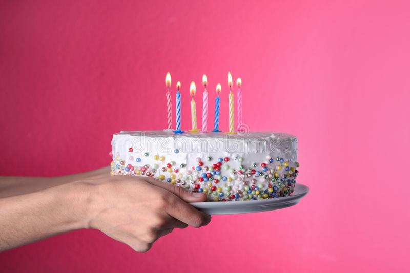 Woman holding birthday cake with burning candles on pink background royalty free stock images