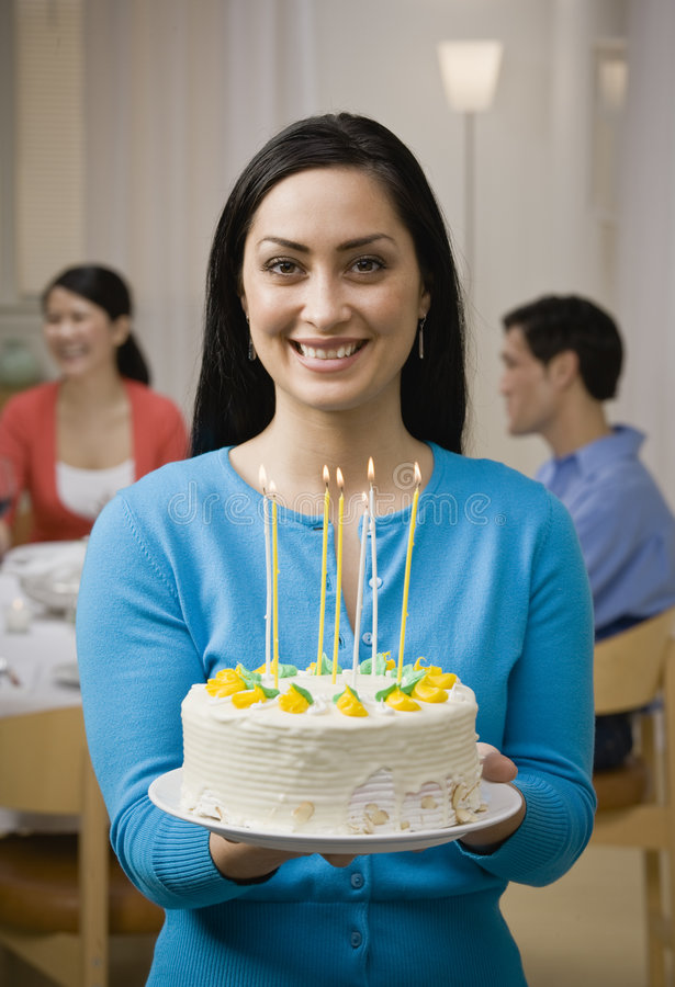 Woman holding birthday cake with candles royalty free stock image